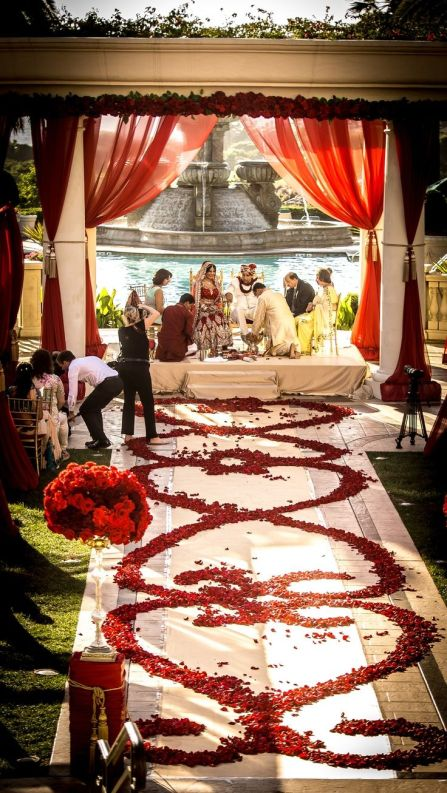 Red Rose Petal Wedding Aisle with Red Drapery and Garland – shared on Colin Cowie Weddings