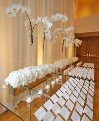 Tall White Orchid Escort Table – shared in a roundup post by MODWEDDING