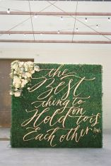 """Gold Script """"The Best Thing to Hold On To Is Each Other,"""" Quote on Green Boxwood Wedding Ceremony Backdrop - shared on Ruffled"""