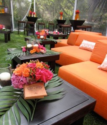 Modern Orange Outdoor Lounge with Dark Wood and Palm Leaf Accents