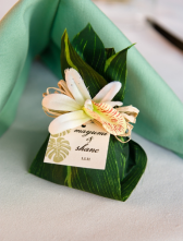 Personalized Wedding Favor Wrapped in a Tropical Leaf with Flower Accent – shared in a roundup post on Mariage