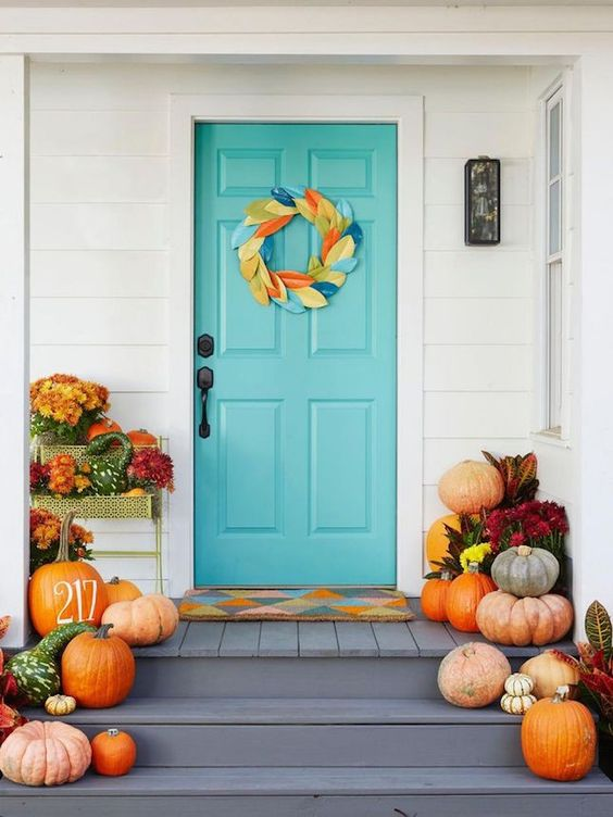 Blue Front Door with Modern Autumn Wreath Décor and Pumpkins – shared in a roundup post by Brit+co
