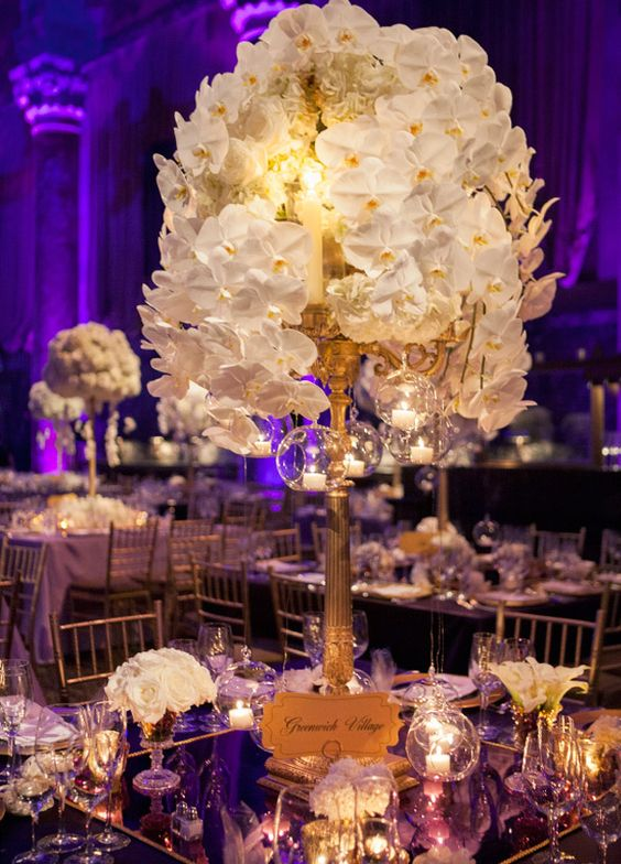 Gold Candlestick Centerpiece with Bubbling White Orchids – created by Colin Cowie Weddings