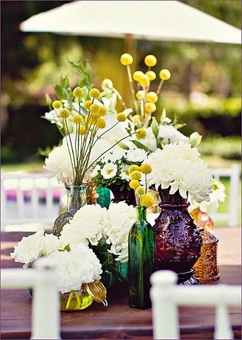 Cluster of Colorful Vintage Glass Bottles with Wildflowers – shared in a roundup post by Deer Pearl Flowers