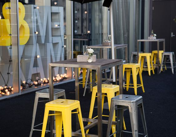 Silver Metal High Top Tables with Silver and Yellow Stools (would be perfect with orange stools instead of yellow) – shared on The Style Co