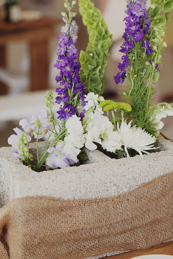 Concrete Block Centerpiece with Burlap Accents and Mixed Flowers – shared on Wedding Chicks