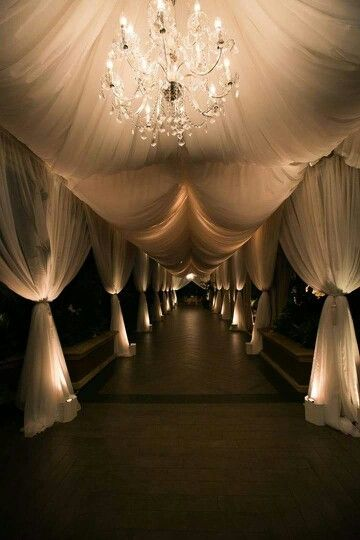 Grand Entrance with White Tent and Drapery featuring Crystal Chandeliers – shared by Inside Weddings