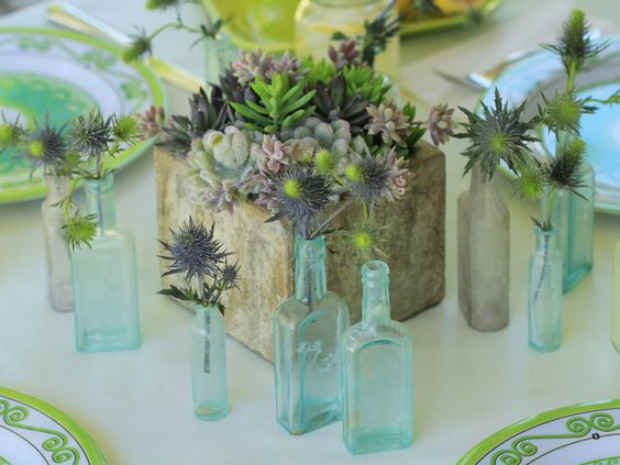 Square Concrete Block Centerpiece with Succulents Surrounded by Small Bud Vases – shared by HGTV