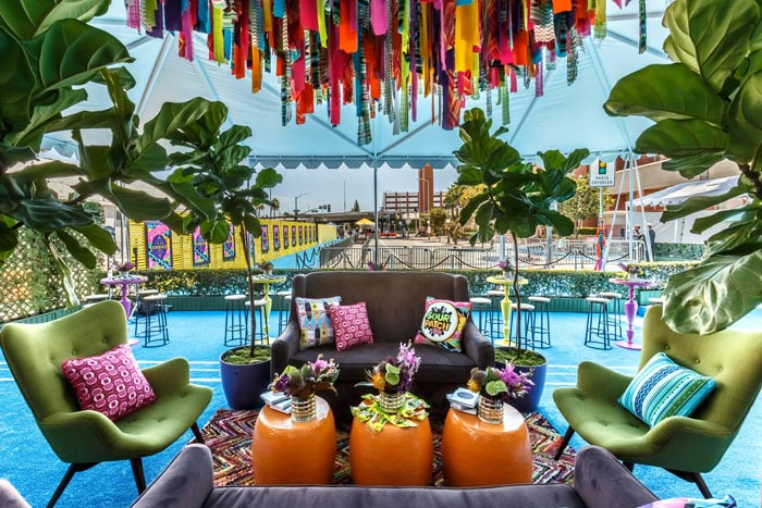 Vibrant Reception Lounge with Hanging Ribbon and Streamer Installation – featured on BizBash
