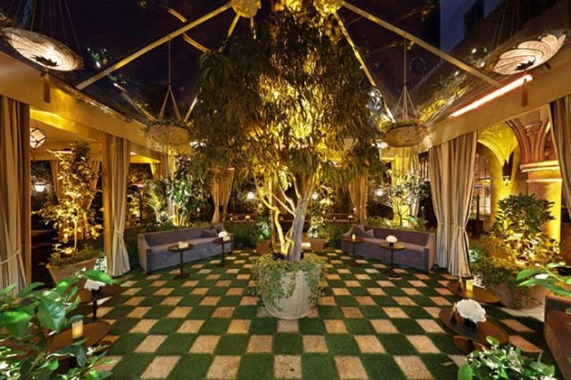 Indoor Garden Reception Lounge Seating with Foliage and Warm Lighting – share by BizBash