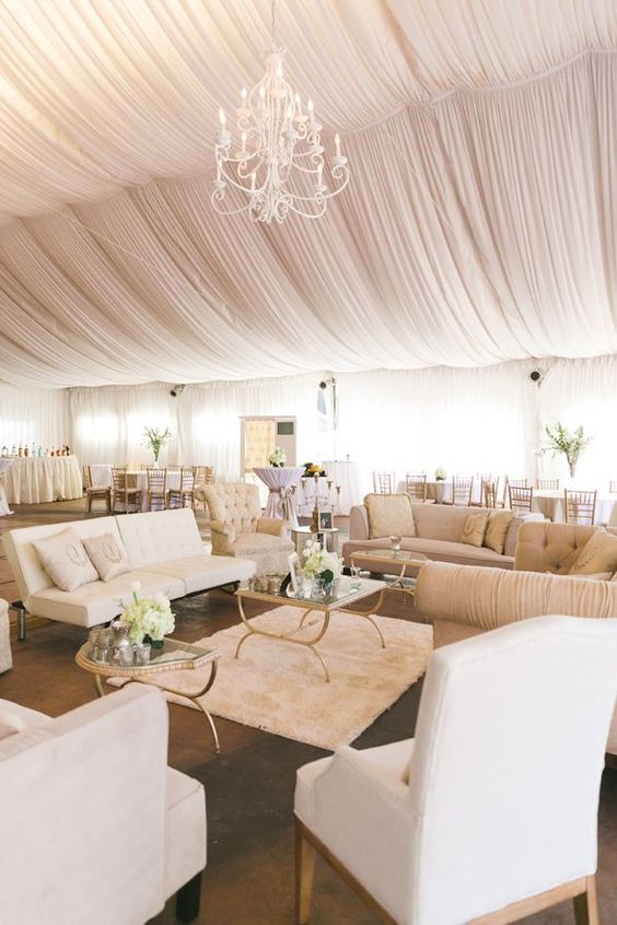 Blush and White Event Tent and Decor with Draped Ceilings, Lounge Groupings, and Chandelier – shared in a round up by MODWEDDING