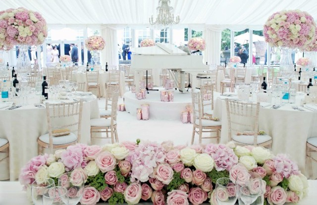 White Baby Grand Piano with Pink Hurricane Vases on a White Circular Stage Under a Crystal Chandelier – by The Angels